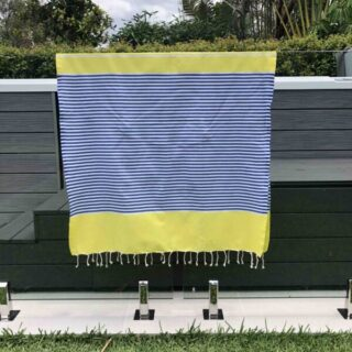 Beach towel hanging over glass pool fence