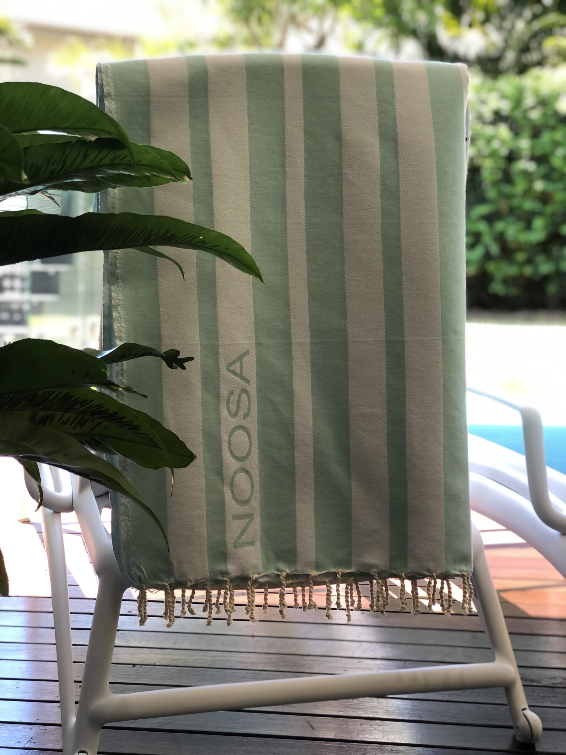 Aquamarine and white striped beach towel hanging by the pool
