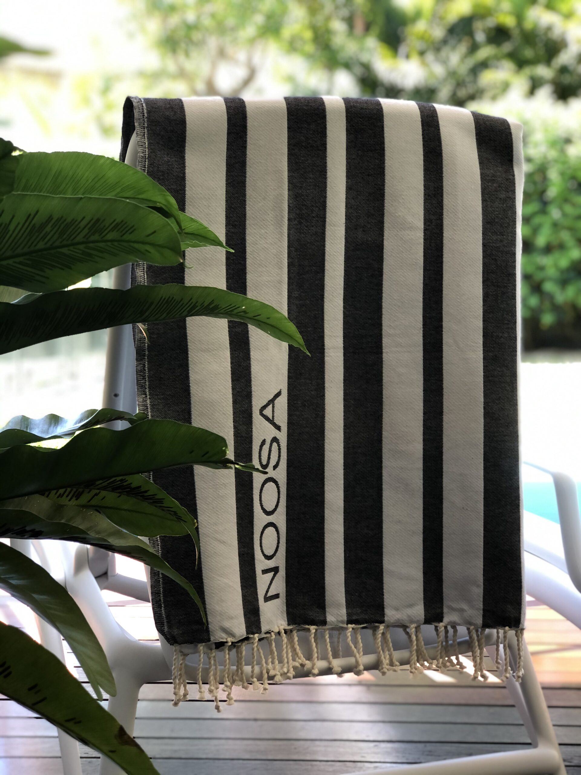 Black and white striped beach towel hanging by the pool