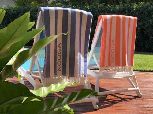 Two beach towels hanging over sun lounges