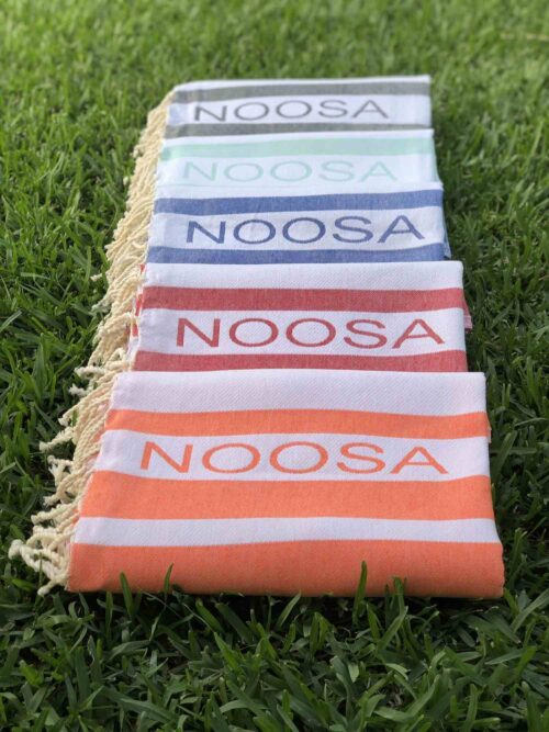 Five folded beach towels laying on the lawn