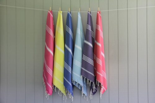 5 beach towels hanging in a row